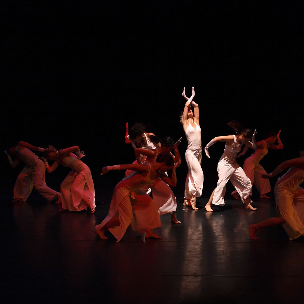 A single dancer lit on the stage with many dancers nearby in the dark