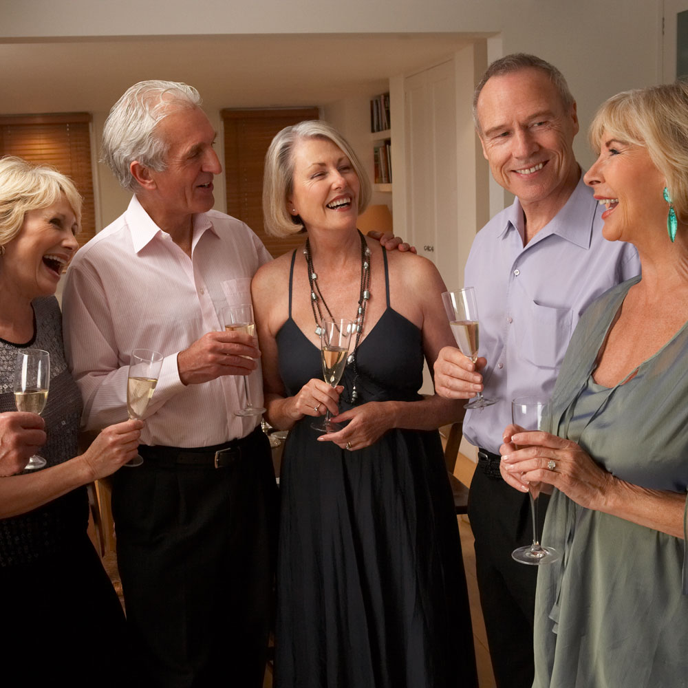 A photo of 3 senior woman and 2 senior men enjoying a glass of white wine and dressed in formal for a theater showing